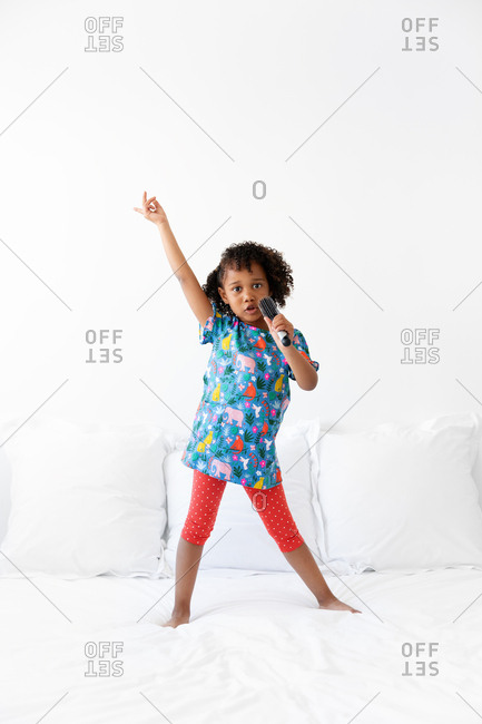 Young child standing on bed singing with hairbrush as a microphone