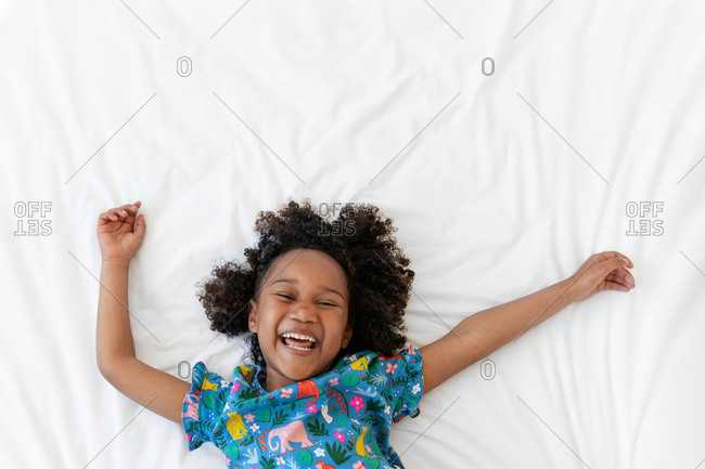 Little girl laughing on white bed with arms up