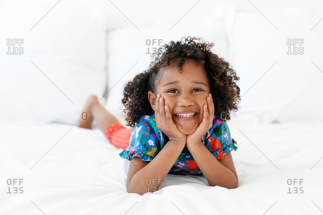 Happy girl lying on bed with chin in hands looking up