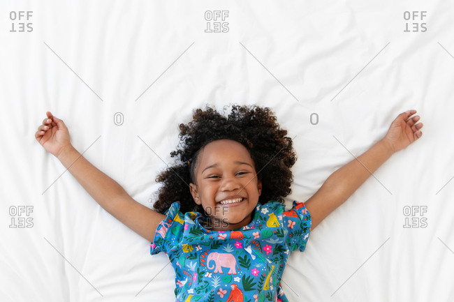 Happy little girl smiling on white bed with arms up