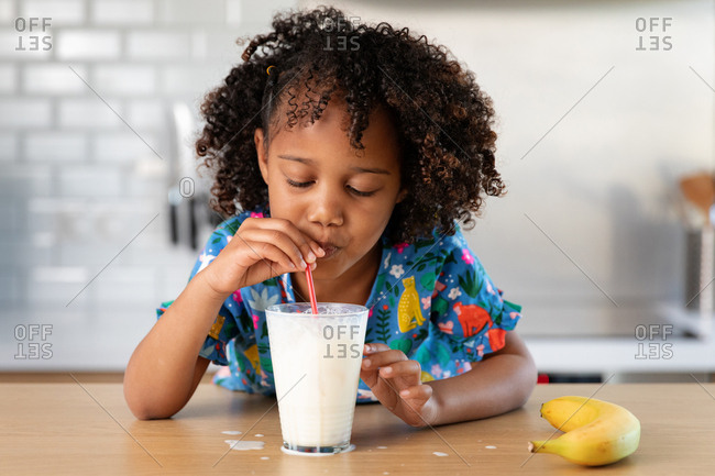 Young girl blowing bubbles in a glass of milk