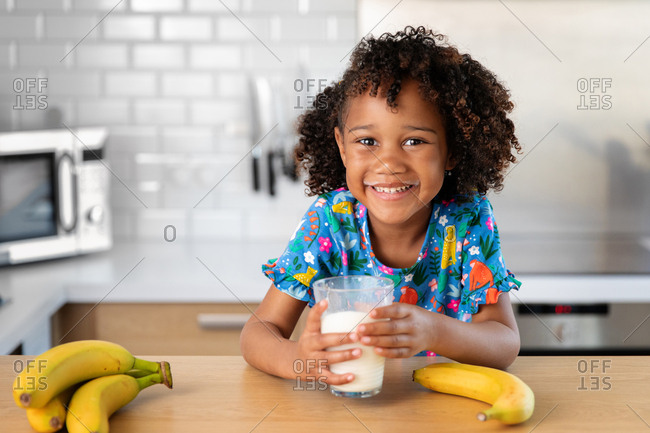 Young girl drinks glass of milk and smiles with milk mustache