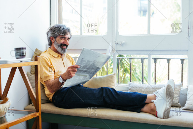 Mature man reading the newspaper in a sofa