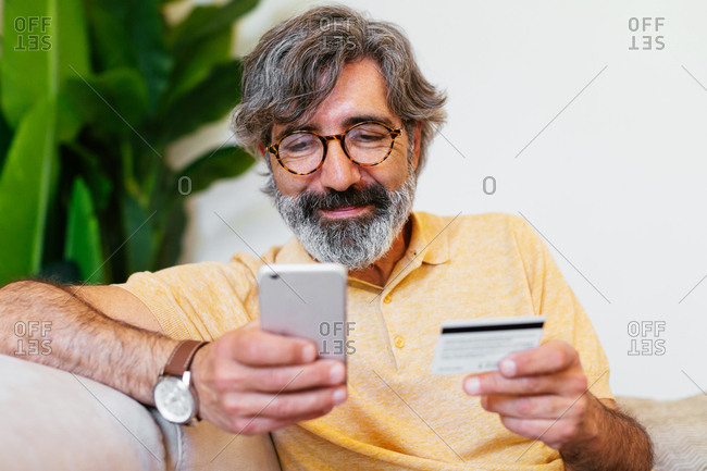 Mature man buying by credit card with a phone on a sofa