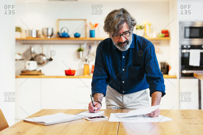 Mature man writing on a notebook at a home office