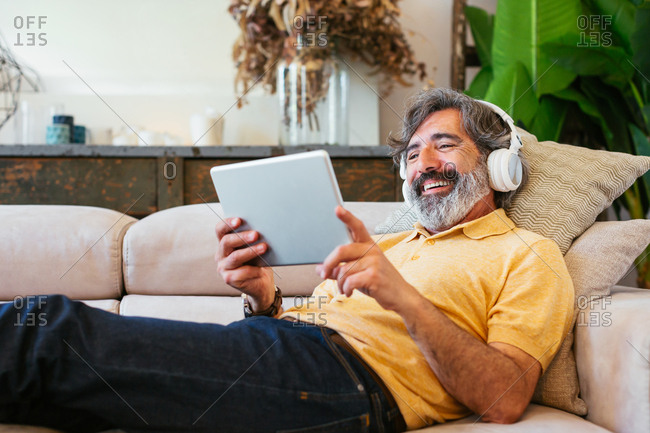 Mature man using a tablet and headphones in a sofa