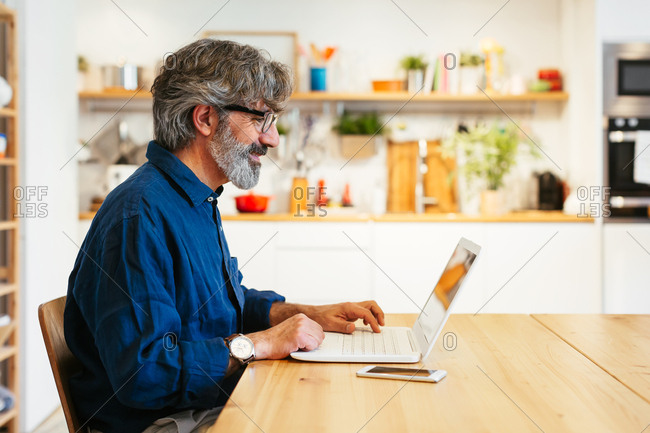 Mature man using a laptop at a home office