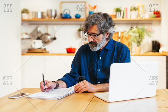 Mature man writing on a notebook next to a laptop at a home office