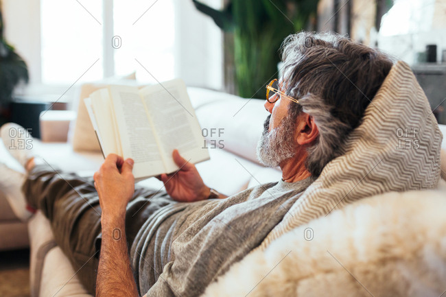 Mature man reading a book while he is lying on the sofa.