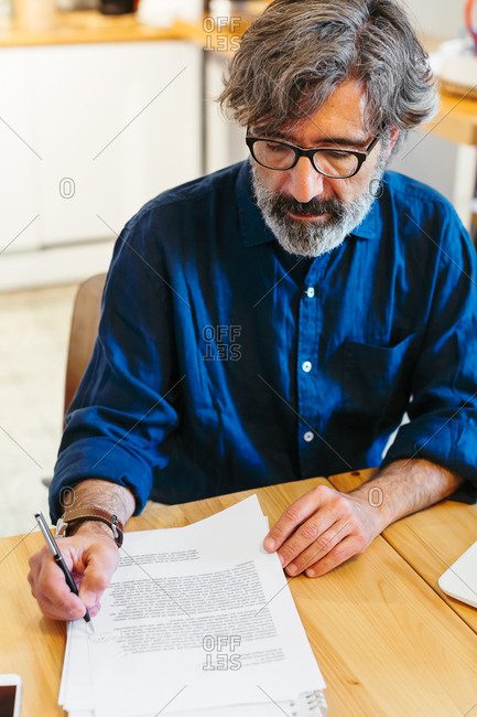 Mature man writing on a paper at a home office