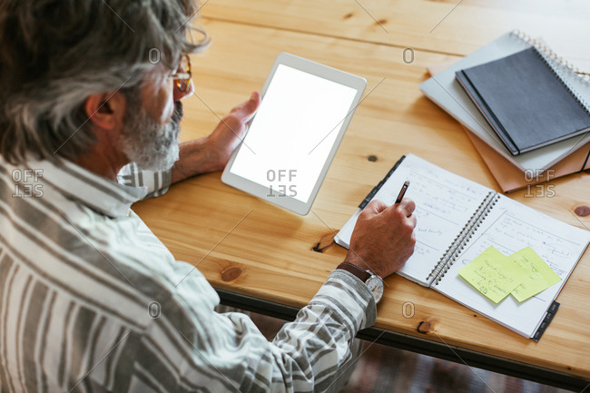 Mature man writing in a notebook and a tablet at a home office