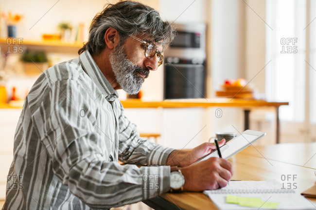 Mature man writing in a notebook and using a tablet at a home office