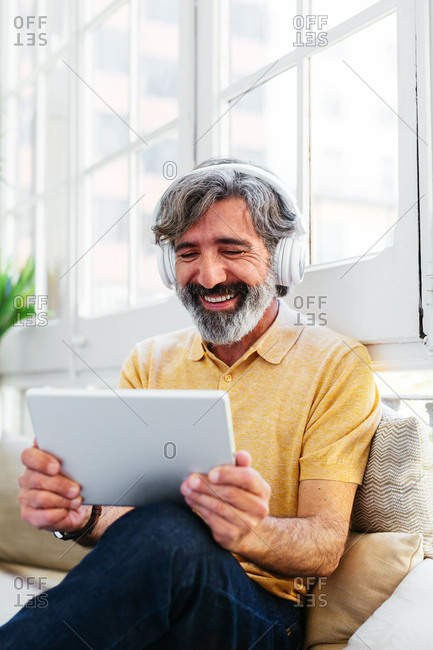 Mature happy man using a tablet with headphones
