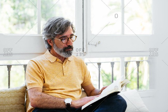 Mature man reading a book at a home office