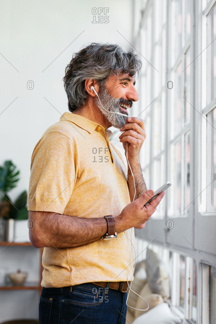 Mature man talking on a mobile phone at a home office