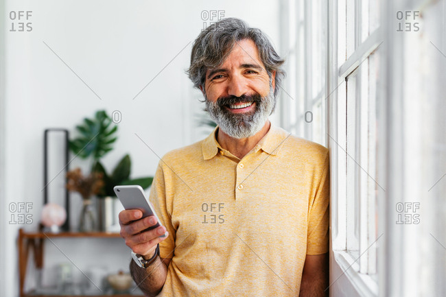 Mature man looking at camera while using a phone at a home office