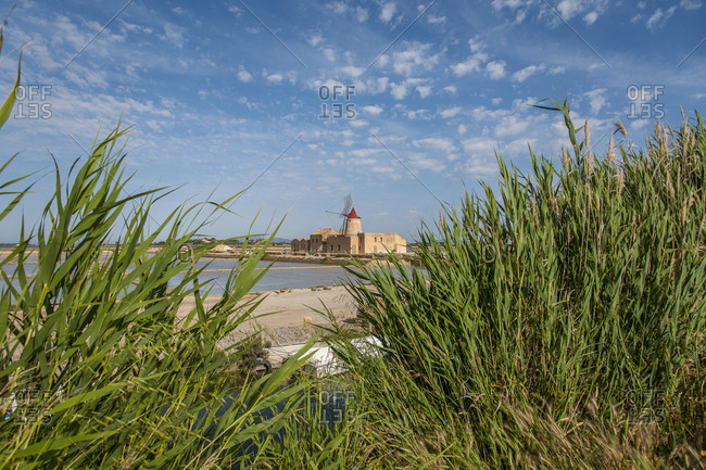 Italy, Sicily, Marsala . Ettore e Infersa saltworks, salt mill and windmill with salt pans. Marsala is famous for salt marshes, and is still home to some of the windmills once used to drain water from the basins (containing ponds). Drawing salt from water remains a slow process