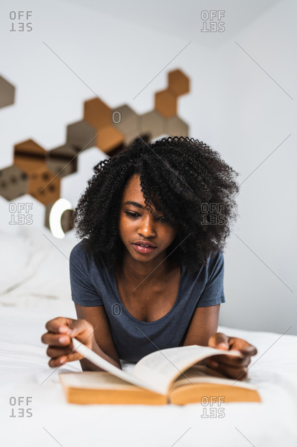 Attractive woman with natural hair reading a book while lying on bed