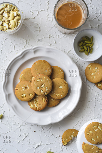 A flat lay image of whole wheat cashew cookies on a plate with some Indian tea to sip and enjoy the evenings