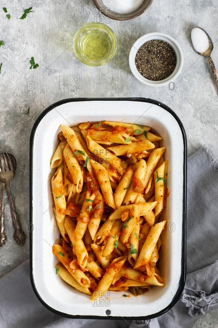 A rectangular tray containing Penne pasta tossed in marinara sauce, perfect for dinner.