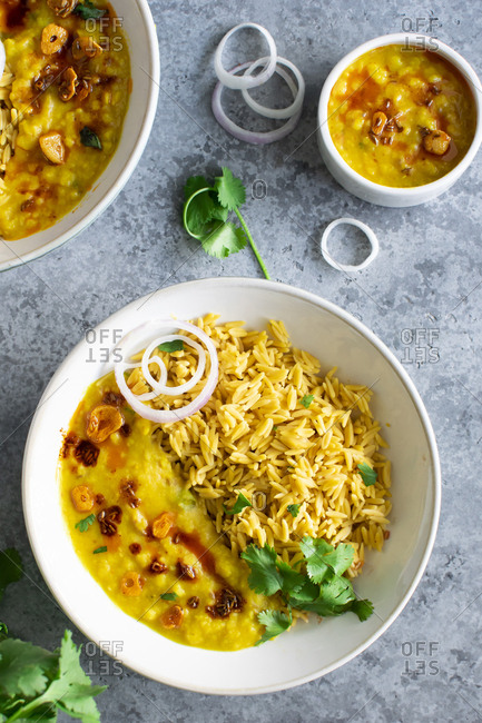 Healthy and  wholesome bowl of Rice and lentil curry (dal tadka) l to enjoy the dinner with some extra onion rings on sides.