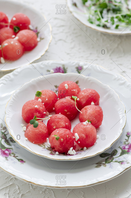 Refreshing juicy watermelon salad on a white plate with a touch of microgreens and feta cheese, perfect salad to enjoy on a silent summer afternoon.