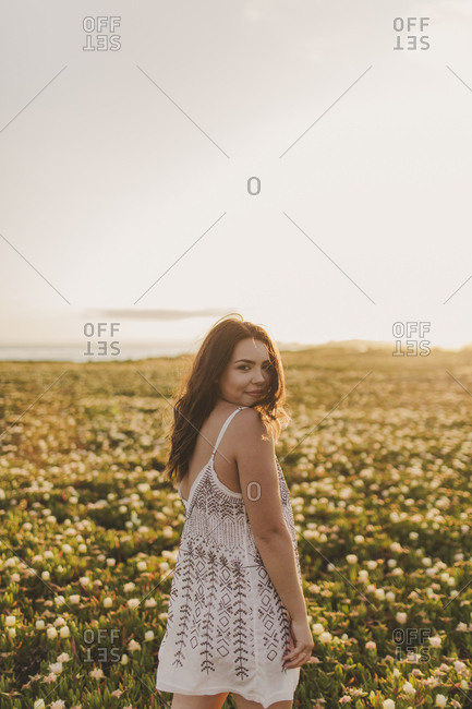Young woman looking over her shoulder in a field at sunset
