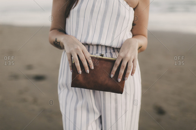 Stylish woman holding brown clutch bag on the beach