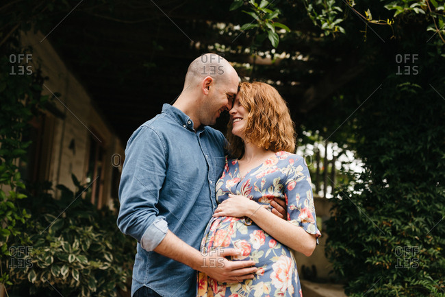 Pregnant couple embracing outdoors
