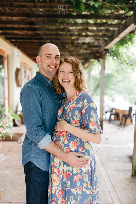 Smiling pregnant couple embracing