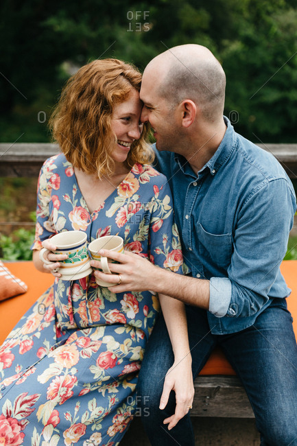Pregnant couple sitting together and enjoying tea outdoors