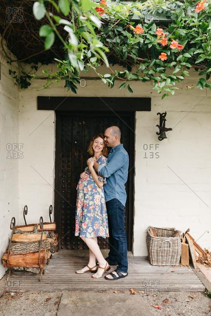 Pregnant couple embracing in front of door