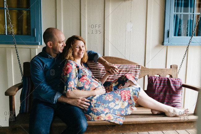Pregnant couple resting on porch swing