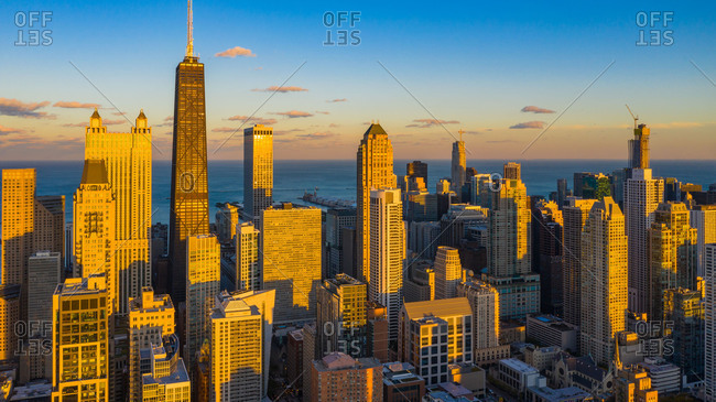 October 15, 2018: Aerial view of skyscrapers posing in the magnificent skyline of downtown Chicago, IL in the United States, amplified in the warm sunlight glow at dusk, with Lake Michigan in the background.