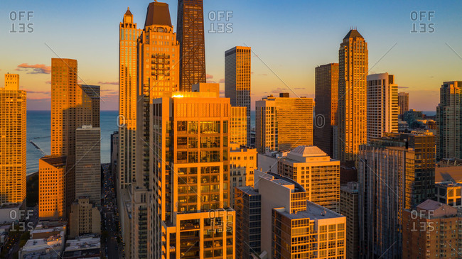 Aerial view of skyscrapers posing in the magnificent skyline of downtown Chicago, IL in the United States, amplified in the warm sunlight glow at dusk, with Lake Michigan in the background.
