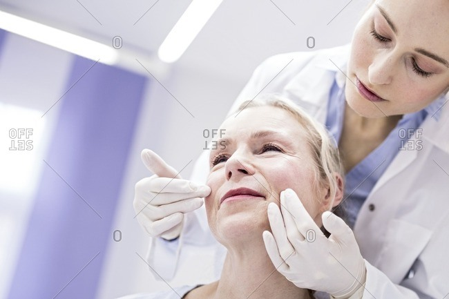 Young female doctor examining patient's face.