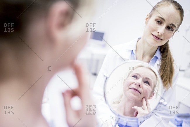 Mature woman looking into a mirror while female doctor standing behind.