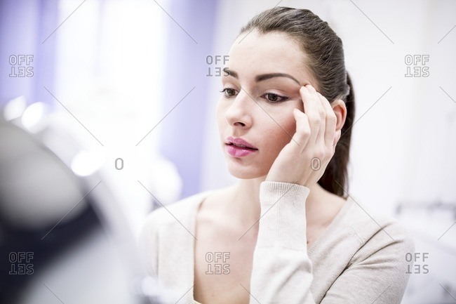 Woman looking in mirror in clinic.