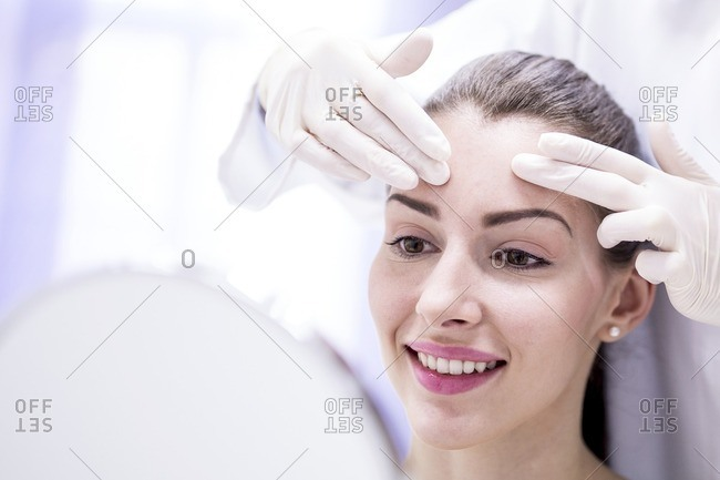Doctor examining young woman's forehead.