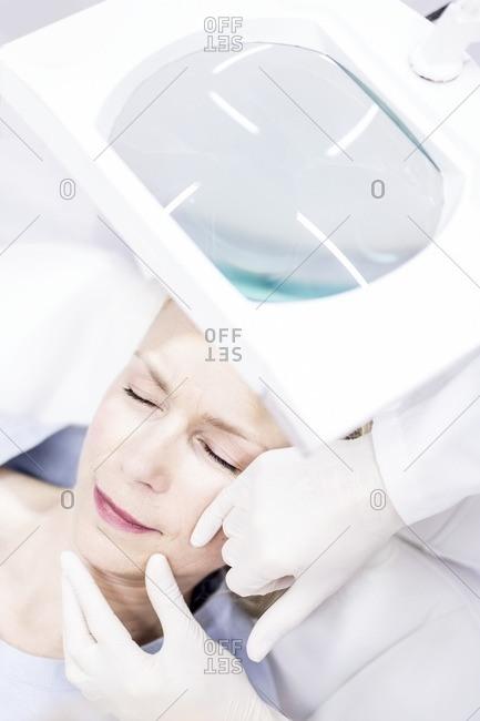 Beauty technician examining woman's facial skin using magnifying glass, close-up.