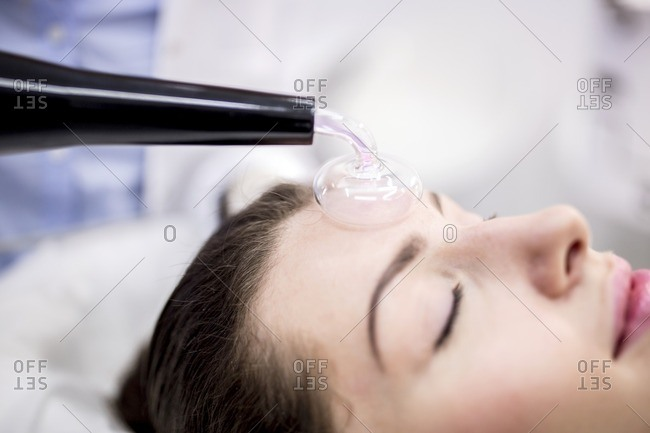 Young woman receiving beauty treatment using a High Frequency Machine in a clinic. The High Frequency Machine uses a glass mushroom shaped electrode filled with argon gas. As the high frequency current is passed down the electrode, an oxygen pocket is created between the electrode and the skin causing the oxygen to become unstable and turn into ozone. Ozone is highly antibacterial and can help in the treatment of acne blemishes.