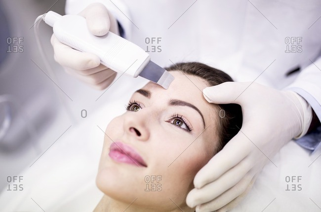 Young woman receiving facial microdermabrasion treatment in clinic, close-up. The cosmetic procedure uses micro crystals to remove dead skin cells. This exfoliating treatment can stimulate the production of collagen and help improve fine lines and acne scarring.