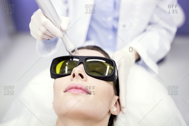 Beauty technician using laser treatment.