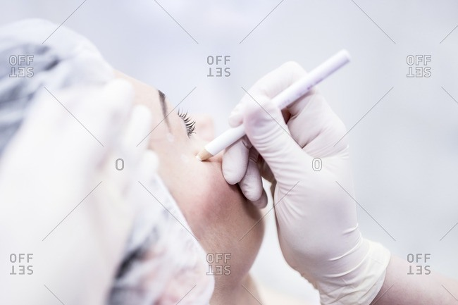 Beauty technician using pencil to mark woman's face for beauty treatment.