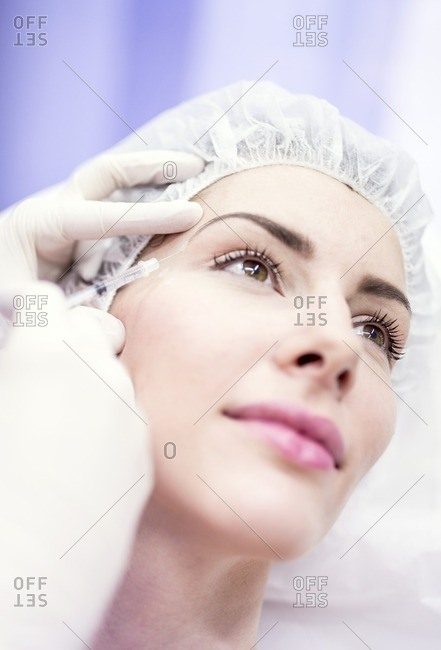 Beauty technician injecting botox into a woman's face. Botox is used medically to treat certain muscular conditions and cosmetically to reduce wrinkles. It is made from a neurotoxin called botulinum toxin and works by temporarily paralyzing muscles.