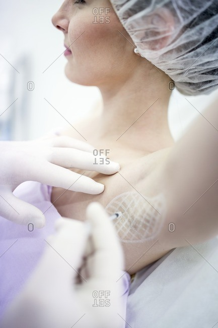 Dermatologist injecting botox in underarm to treat excessive sweating, close-up.