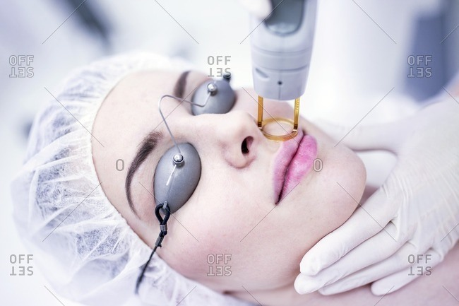 Young woman having laser hair removal treatment on face, close-up.