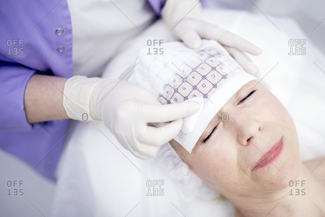 Dermatologist tracing grid paper on mature woman's forehead for thermite therapy to soften wrinkles.