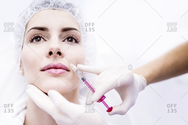 Young woman having a plasma and hyaluronic acid injection in her face to rejuvenate and smooth skin, close-up.