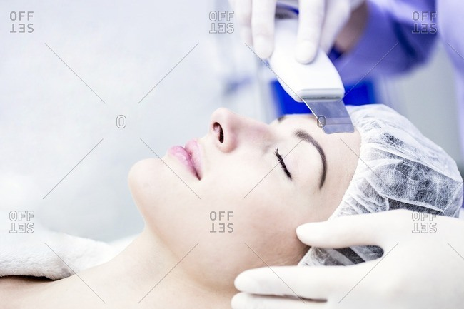 Young woman receiving facial microdermabrasion treatment in clinic, close-up. Young woman receiving facial microdermabrasion treatment in clinic, close-up. The cosmetic procedure uses micro crystals to remove dead skin cells. This exfoliating treatment can stimulate the production of collagen and help improve fine lines and acne scarring.